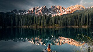 ilhan-eroglu-sony-alpha-7RIII-lady-sitting-on-rock-in-front-of-majestic-tree-lined-landscape-with-mountains