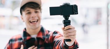 Imagem de uma pessoa a filmar-se a si mesma com a ZV-E10 com uma pega encaixada