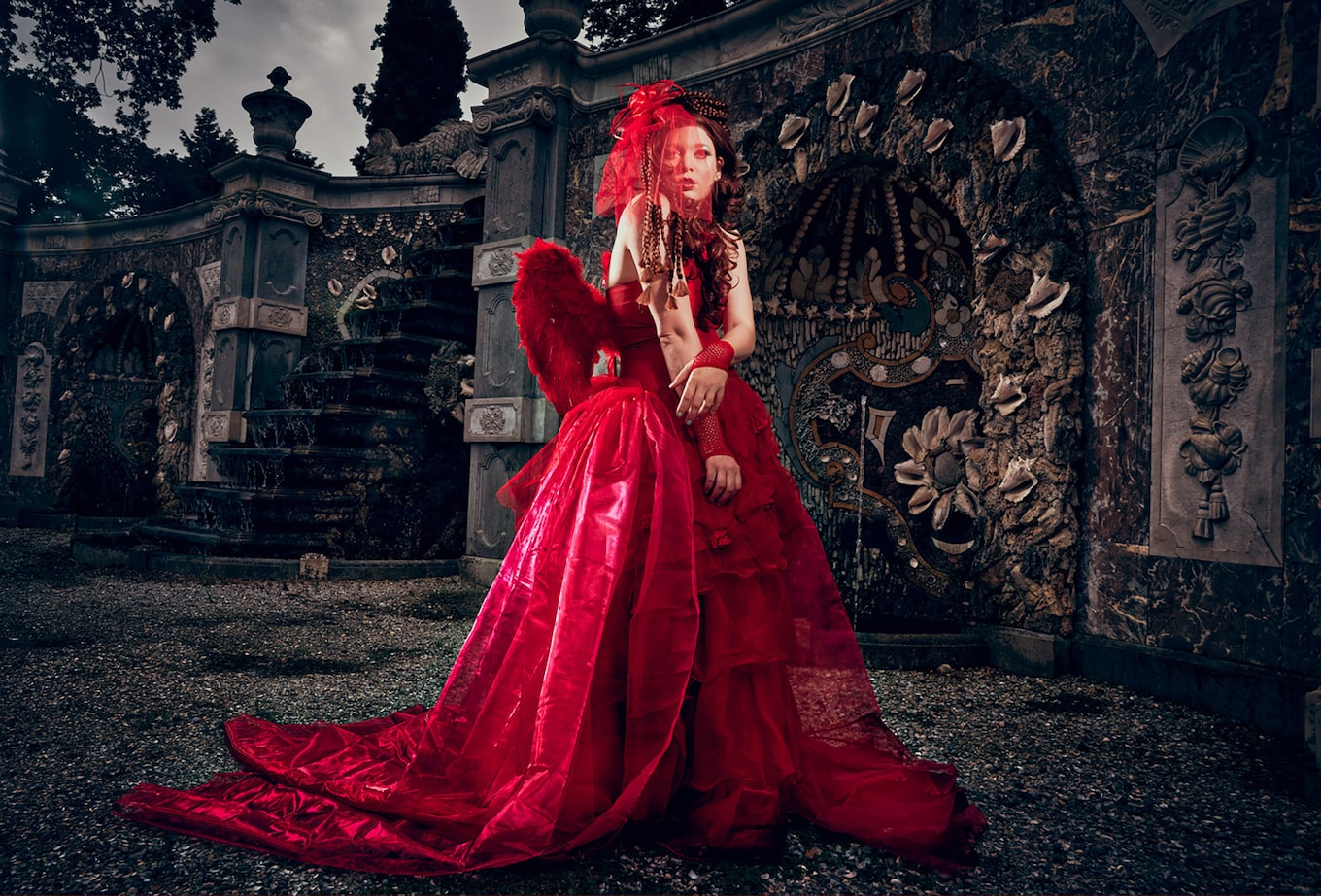 Frank-Doorhof-sony-alpha-7RII-model-in-red-dress-in-front-of-gothic-castle-backdrop