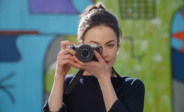 Retrato de uma mulher a tirar fotografias no exterior